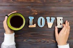 Mains femelles avec du café et les biscuits en forme de coeur sur la table en bois, vue supérieure Concept d'amour Lettre d'amour Images stock