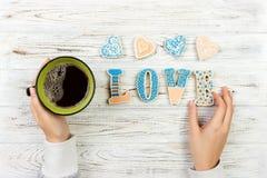 Mains femelles avec du café et les biscuits en forme de coeur sur la table en bois, vue supérieure Concept d'amour Lettre d'amour Images libres de droits