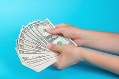 Mains femelles avec l'argent sur un fond bleu Concept d'économie Affectation d'argent photographie stock libre de droits