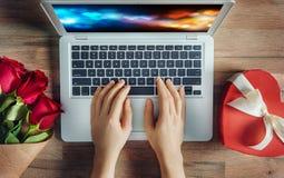 Mains femelles avec l'ordinateur portable Photo stock