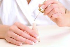 Mains femelles avec la bouteille de balai et d'émail Images stock