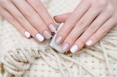 Mains femelles avec la conception blanche de clou Image libre de droits