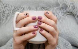 Mains femelles avec la conception rose foncée de clou photographie stock libre de droits