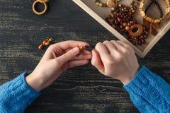 Mains femelles avec la fabrication colorée de collier de perles Photographie stock libre de droits