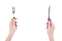 Mains femelles avec la fourchette et le couteau d'isolement sur le blanc Photo libre de droits