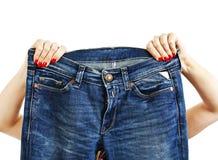 Mains femelles avec la manucure rouge tenant des blues-jean Photographie stock