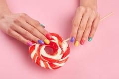 Mains femelles avec le grand lollypop Images stock