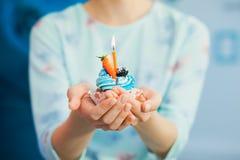 Mains femelles avec le petit gâteau d'anniversaire décoré du fruit effectuer Image stock