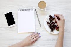 Mains femelles avec le smartphone, le latte, le carnet, les fraises et les cerises sur le fond en bois blanc, vue supérieure Conf Image stock