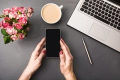 Mains femelles avec le smartphone, les fleurs, la tasse de café et l'ordinateur portable sur la table grise Vue supérieure Photo libre de droits