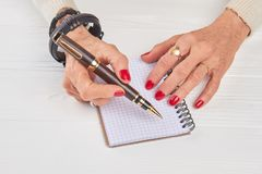 Mains femelles avec le stylo et le carnet de luxe Image libre de droits
