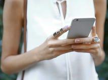 Mains femelles avec le téléphone et les anneaux élégants Images libres de droits