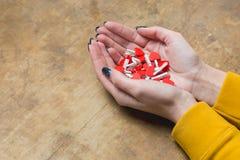 Mains femelles avec les coeurs rouges sur une table en bois Images libres de droits