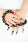Mains femelles avec les perles noires dans les doigts sur le fond blanc Photos stock