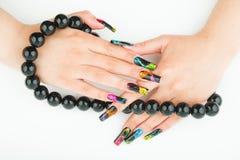 Mains femelles avec les perles noires dans les doigts sur le fond blanc Photo stock