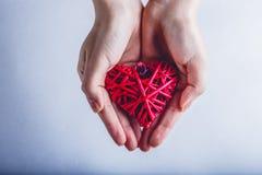 Mains femelles avec un coeur rouge romantique enlacé de vintage sur un fond de neige Concept d'amour et de St Valentine Photos stock