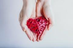 Mains femelles avec un coeur rouge romantique enlacé de vintage sur un fond de neige Concept d'amour et de St Valentine Photographie stock