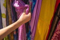 Mains femelles choisissant des vêtements dans la stalle du marché Photographie stock libre de droits