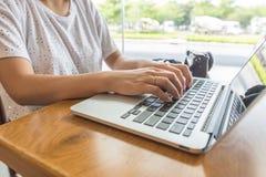 Mains femelles dactylographiant sur l'ordinateur portable près de la caméra images stock