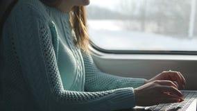 Mains femelles dactylographiant sur le clavier de l'ordinateur portable dans le train Femme causant avec des amis pendant le dépl Photo stock