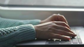 Mains femelles dactylographiant sur le clavier de l'ordinateur portable dans le train Femme causant avec des amis pendant le dépl Image stock
