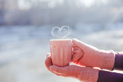 Mains femelles dans des mitaines tenant la tasse avec le thé ou le café chaud avec la forme de coeur Photographie stock