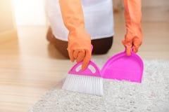 Mains femelles dans les gants balayant une brosse de tapis, concept de nettoyage de service, plan rapproché Image libre de droits
