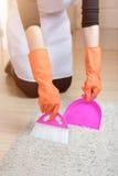 Mains femelles dans les gants balayant une brosse de tapis, concept de nettoyage de service, plan rapproché Images libres de droits