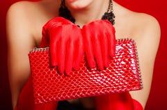Mains femelles dans les gants rouges tenant un embrayage rouge image stock