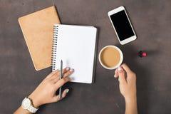 Mains femelles de configuration d'espace de travail plat de femmes, café, carnet, smartph Photo stock