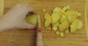 Mains femelles de femme au foyer coupant en tranches des pommes de terre en morceaux dans la cuisine image stock