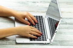Mains femelles de plan rapproché de la jeune femme d'affaires à l'aide de l'ordinateur portable sur Rus images stock