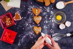 Mains femelles de vue supérieure décorant les biscuits faits maison dans la forme du coeur comme cadeau pour l'amant le jour du ` Images libres de droits