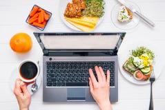 Mains femelles de vue supérieure travaillant à l'ordinateur portable et au café de boissons sur la table en bois blanche servie a Photos stock