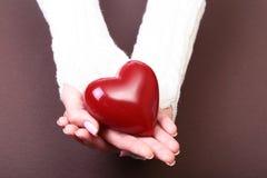 Mains femelles donnant le coeur rouge, d'isolement sur le fond d'or Image libre de droits
