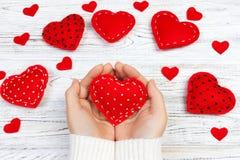 Mains femelles donnant le coeur rouge Fond de jour de Valentine Images stock