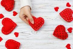 Mains femelles donnant le coeur rouge Fond de jour de Valentine Photos stock