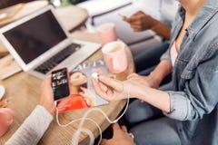 Mains femelles douces tenant les écouteurs et le téléphone images stock