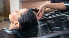 Mains femelles en gros plan des cheveux de lavage de coiffeur professionnel à la femme de brune après coloration banque de vidéos