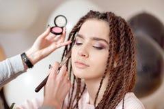 Mains femelles en gros plan faisant le maquillage professionnel sur le visage de jeune femme photographie stock libre de droits