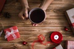 Mains femelles enveloppant des cadeaux de Noël en papier et les attachant avec des fils rouges et de blanc et une tasse de thé Photographie stock libre de droits