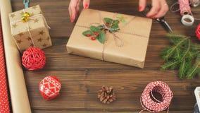 Mains femelles enveloppant le cadeau de Noël en papier écologique de métier sur le backround en bois foncé banque de vidéos