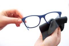 Mains femelles essuyant des lunettes avec un tissu de microfiber photos stock