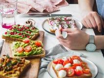 Mains femelles et sandwichs végétariens sur la table photos stock