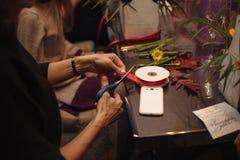 Mains femelles faisant un bouquet Photographie stock