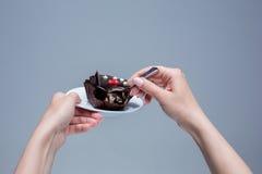 Mains femelles gardant le gâteau avec la cuillère sur le gris Photo stock