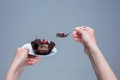 Mains femelles gardant le gâteau avec la cuillère sur le gris Photographie stock