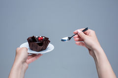 Mains femelles gardant le gâteau avec la cuillère sur le gris Images libres de droits