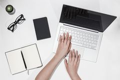 Mains femelles imprimant le texte sur l'ordinateur portable Vue supérieure d'espace de travail moderne avec l'ordinateur portable Image libre de droits