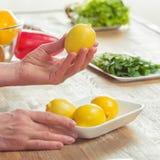 Mains femelles inspectant des citrons Images stock
